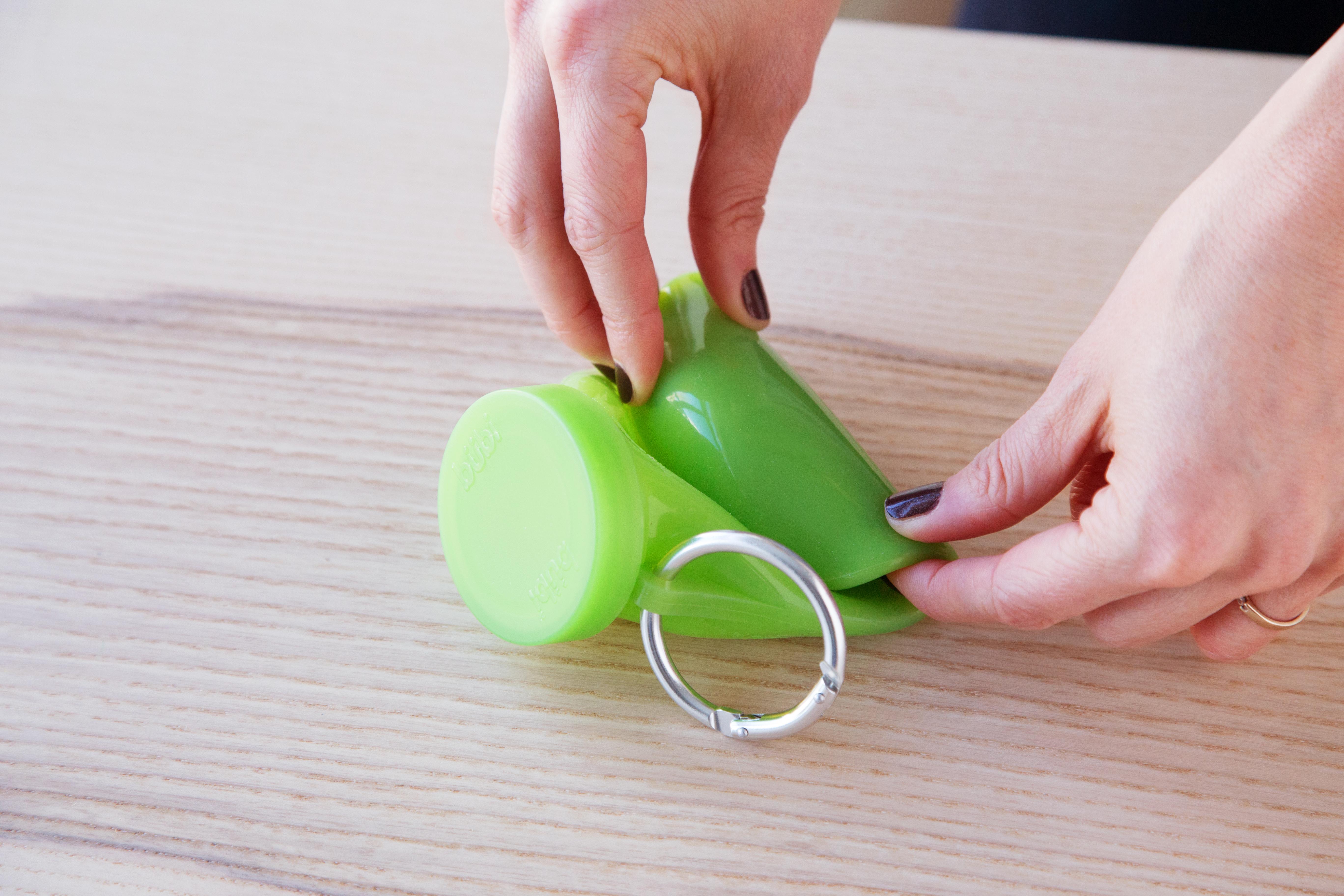 A woman is seen rolling a green bubi water bottle
