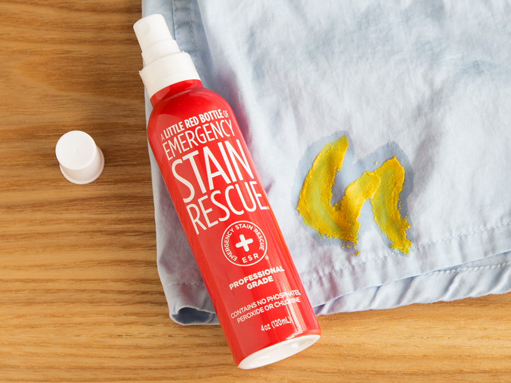 The hate Stain's co's little red bottle of emergency stain remove sits next to a shirt stained with mustard