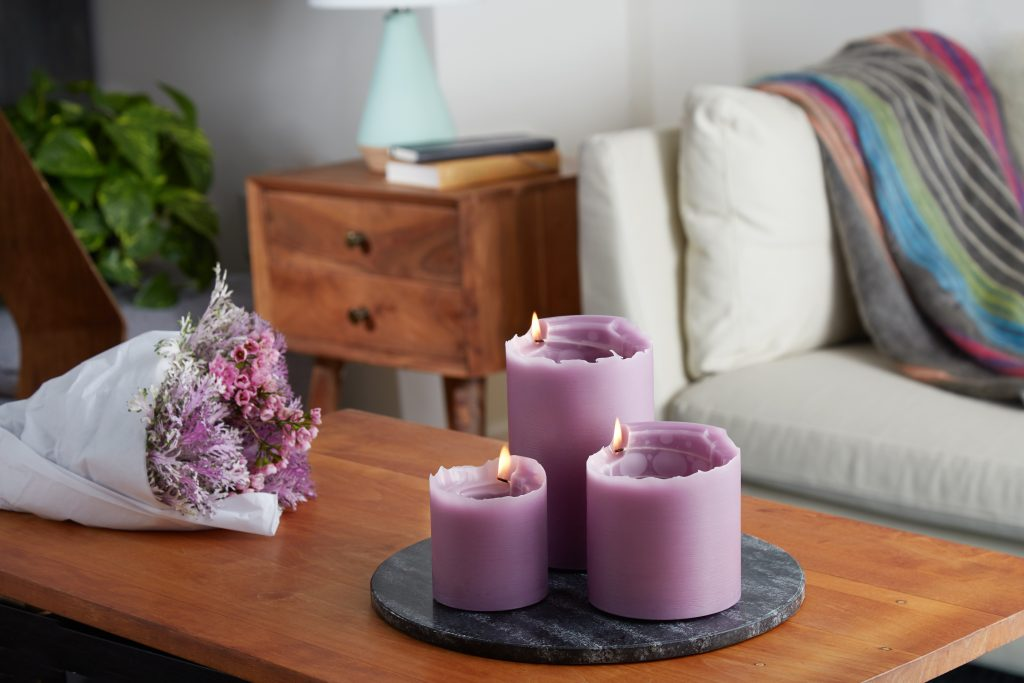 3 lavender Spiral Light candles are seen burning on a coffee table next to a bouquet of flowers