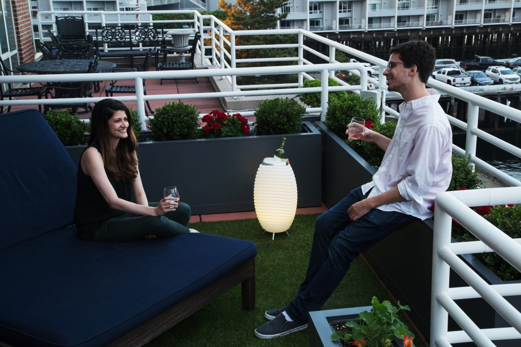 Two friends sit on a patio, enjoying wine and music as a bottle of wine chill in a Kooduu wine cooler speaker