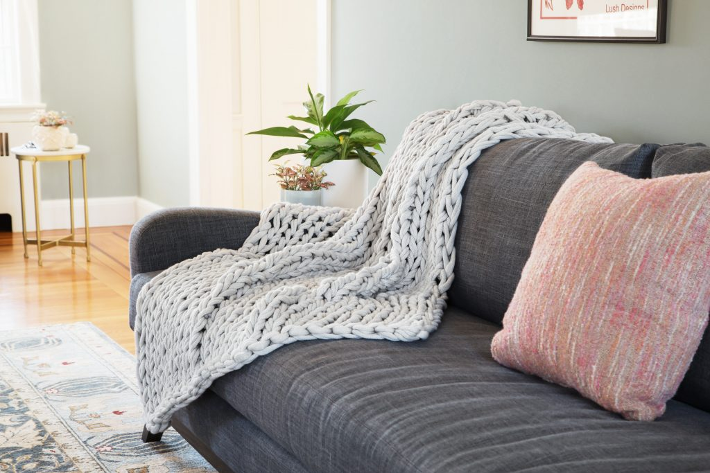 A cozy knit grey cable throw from Bedford Collections sits on a couch