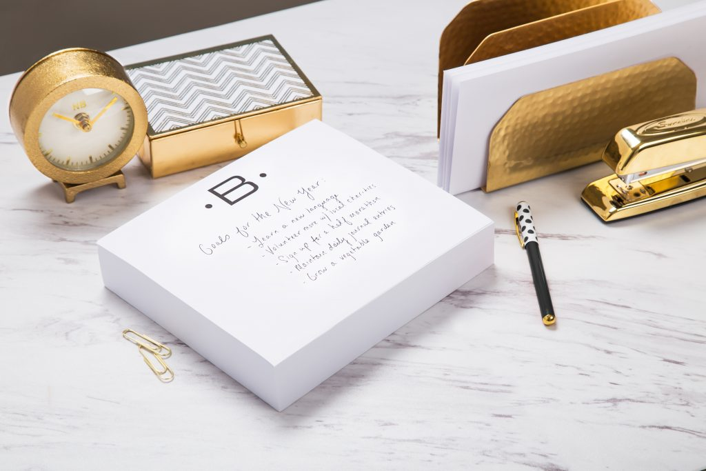 A 'B' monogrammed stationary pad from Black Ink with a list of new year's goals sits on a desk