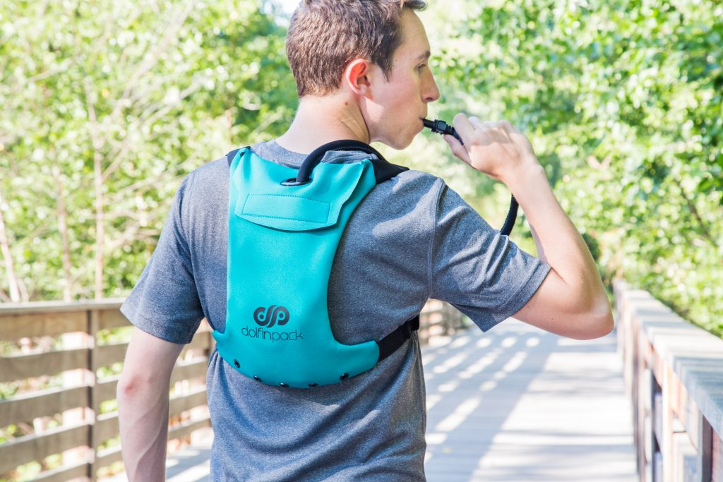 A man is seen drinking from a Dolfinpack multi-sport hydration pack while on the trail