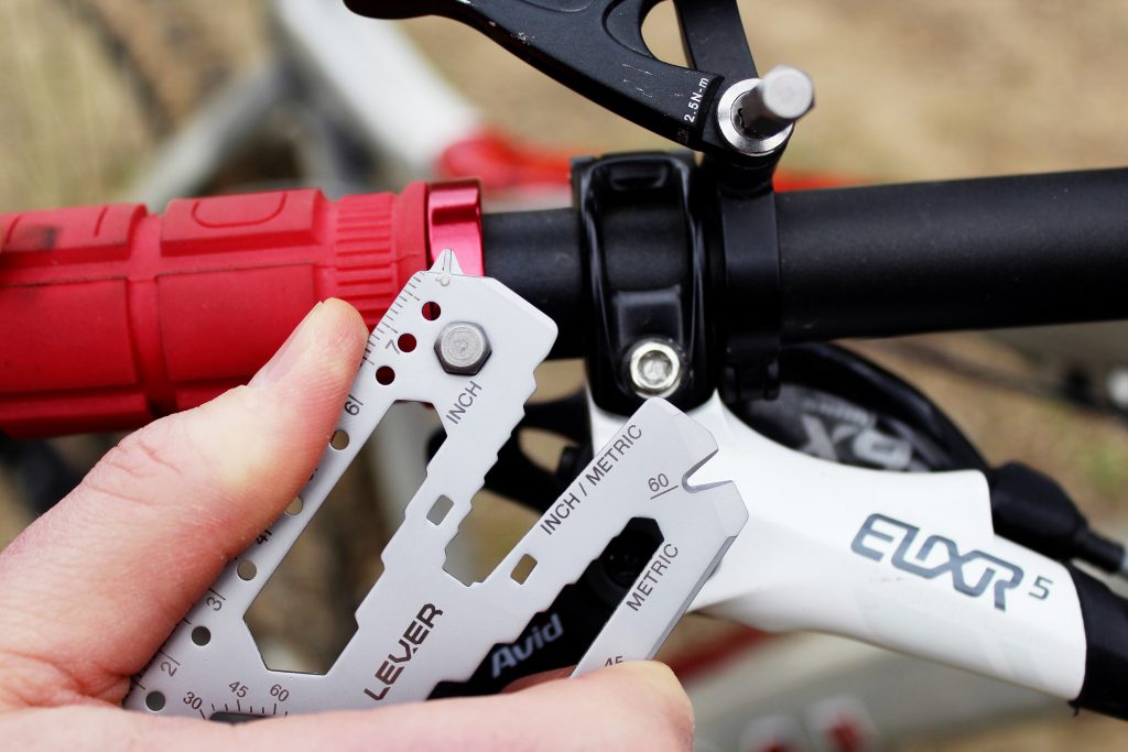 A person is seen fixing a bike using Lever Gear's pocket multitool