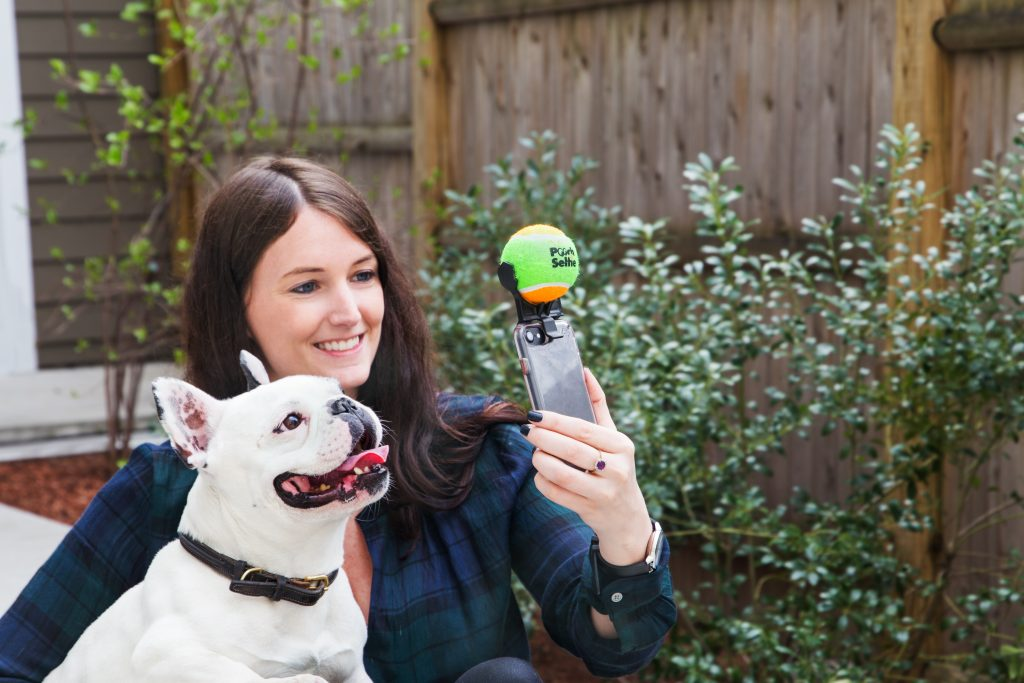 A woman is seen taking a selfie with her french bulldog using Pooch Selfie