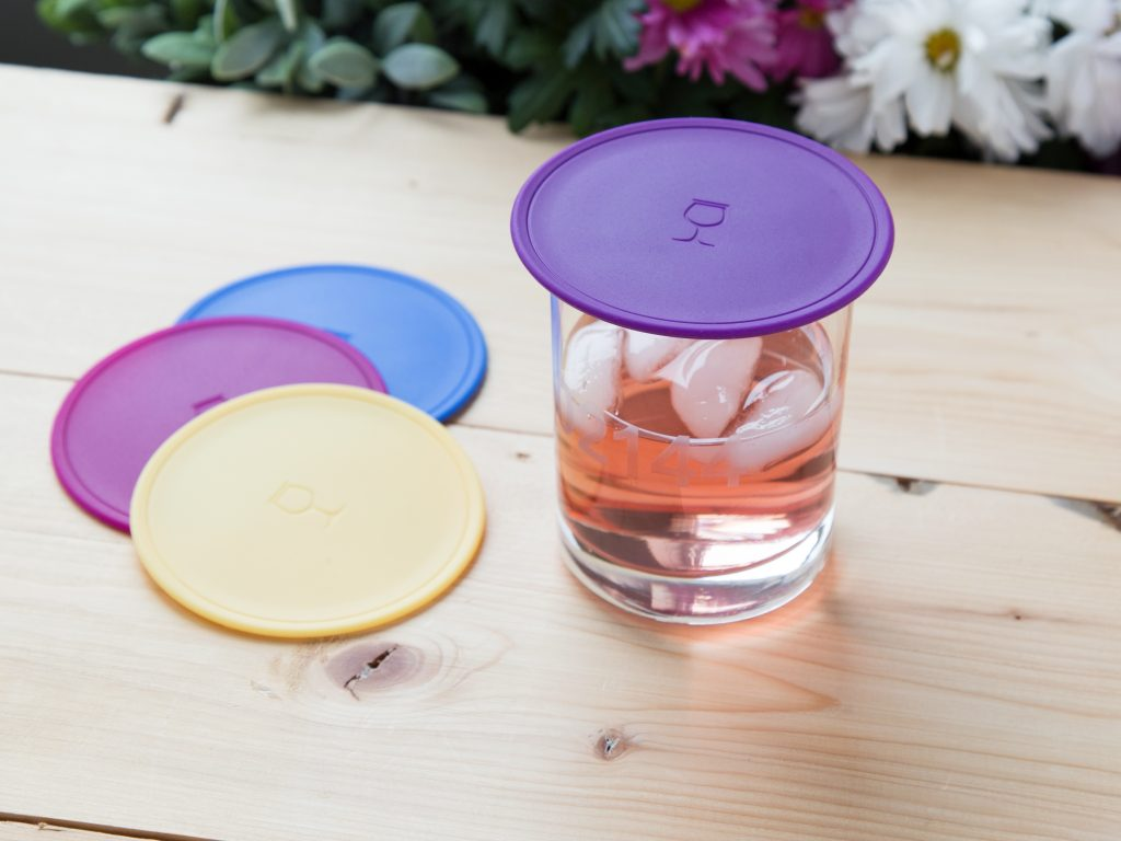 A glass of rose wine is protected from bugs with a purple Drink Tops insect shield