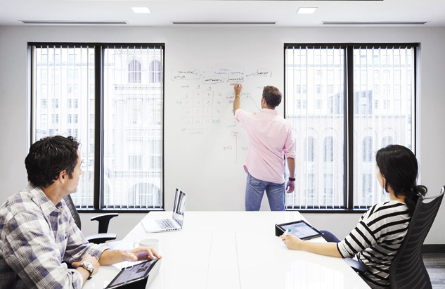 A man is seen writing on the wall of a conference room during a meeting using IdeaPaint's whiteboard paint