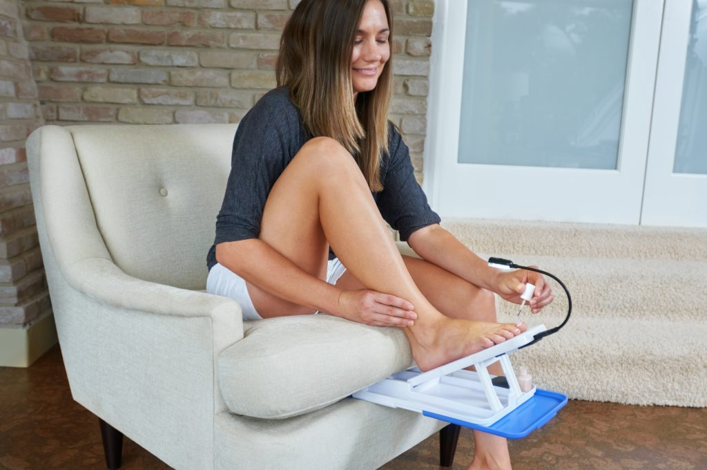 A woman is seen sitting on a chair using Stedi Pedi's home pedicure kit to paint her toes