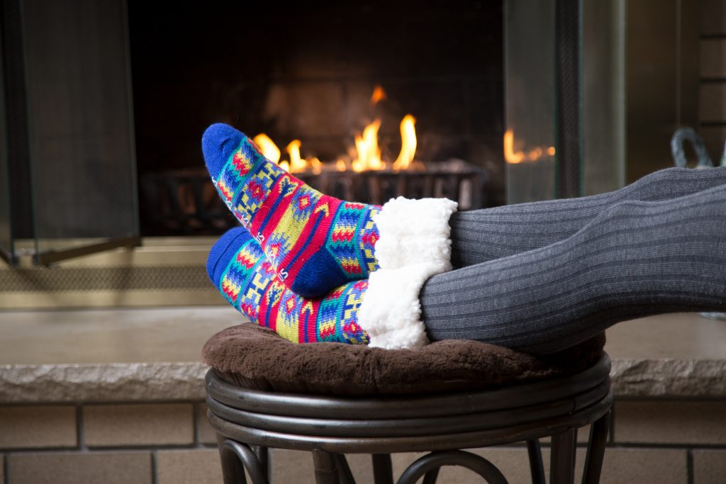 A teen is seen lounging in front of a fireplace wearing brightly patterned PUDUS slipper socks