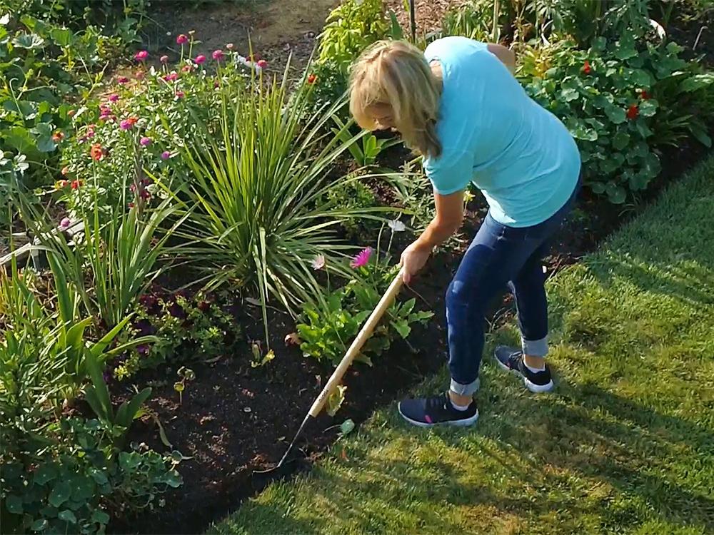 A woman is seen edging her flower bed with Kwik Edge's garden edger