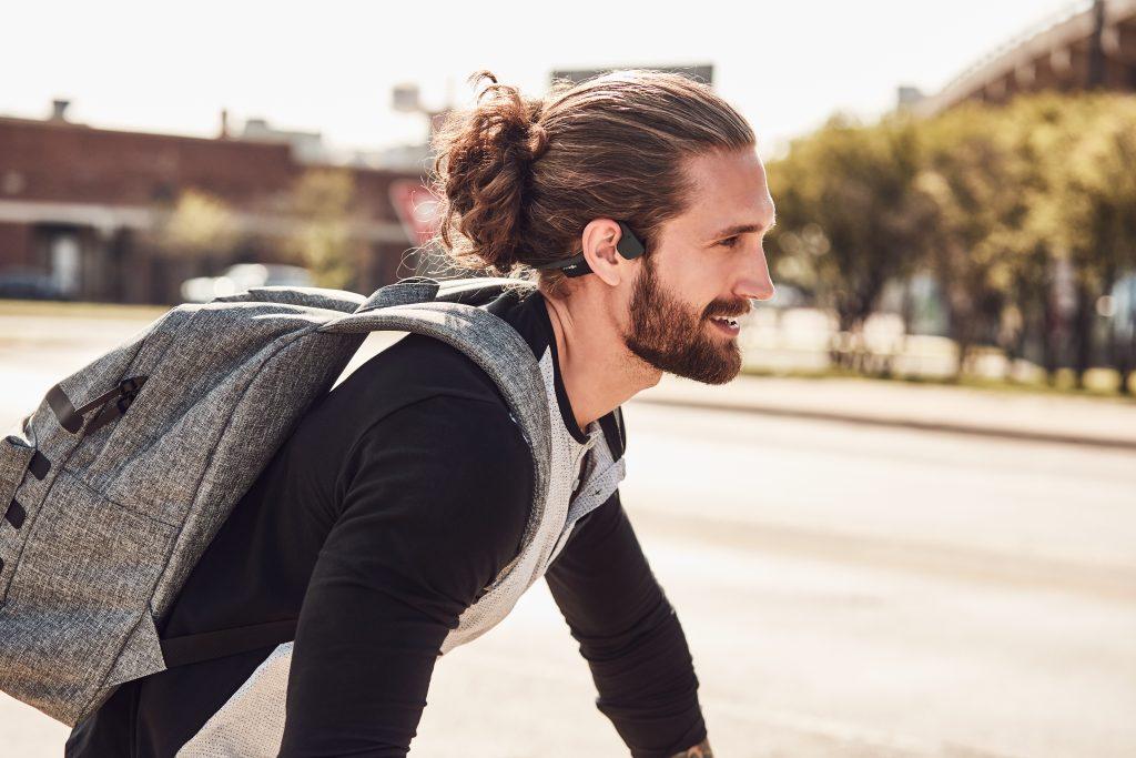 A man is seen wearing AfterShokz Trekz air headphones while riding a bike