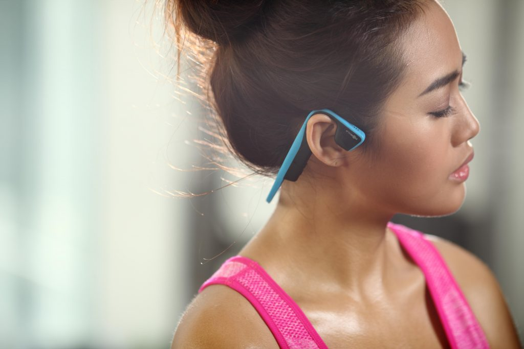 A woman is seen working out wearing AfterShokz Trez Titanium earphones