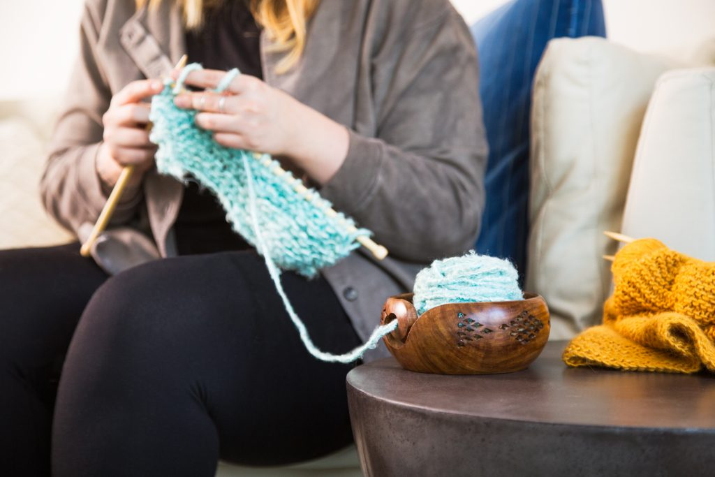 A woman is seen knitting something turquoise using her handcrafted geometric knitting bowl from Darn Good Yarn