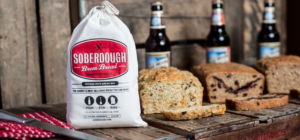 SoberDough beer bread mix is seen next to 3 loaves of beer bread made with Blue Moon beer