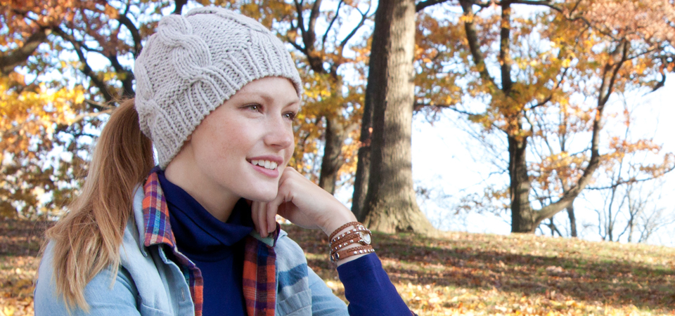 A woman is seen in a park during fall wearing a knitted ponytail hat from Peekaboo Ponytail