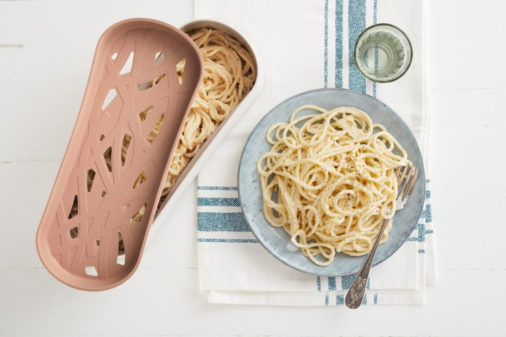 A plate of freshly cooked pasta sits next to Lékué's microwavable pasta cooker