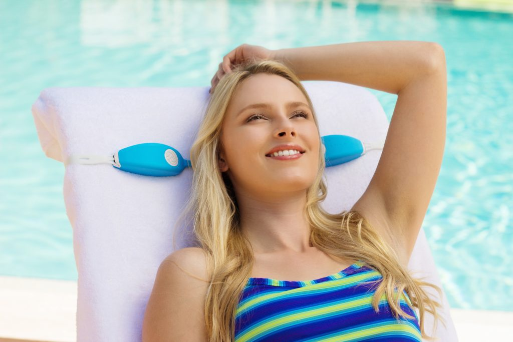 A woman is seen lounging by the pool, enjoying music from her SunTunes near-ear bluetooth speakers