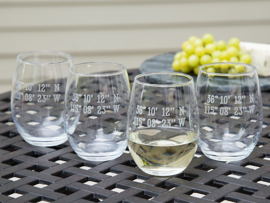 Four custom latitude & longitude stemless wine glasses from Susquehanna Glass Company sit on a patio table