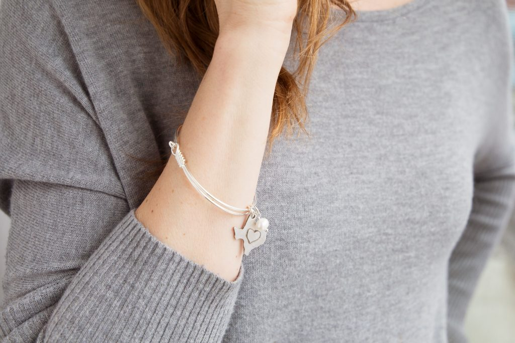 A woman is seen wearing a Texas Hometown Love bangle from The Vintage Pearl