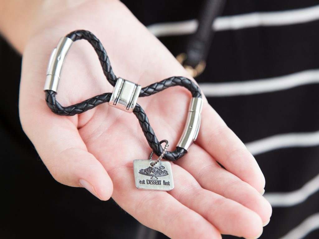 A My-Storytellers infinity loop keychain with a charm that says 'Eat dessert first' is seen in the palm of a woman's hand