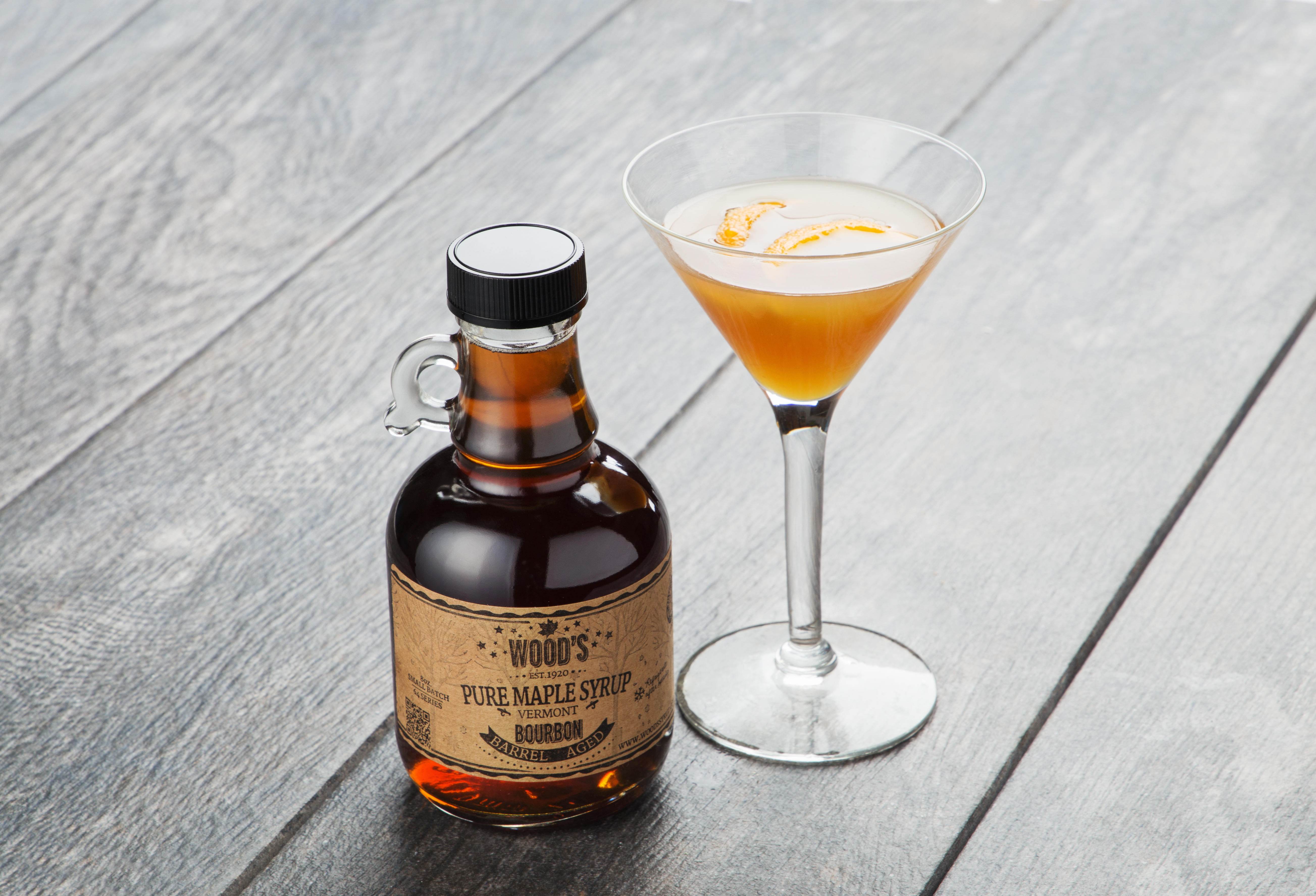 A bottle of Bourbon-infused Wood's Maple syrup sits next to a martini