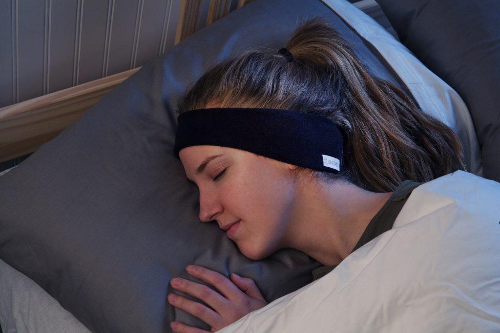 A woman is seen sleeping soundly thanks to SleepPhones wireless headphones
