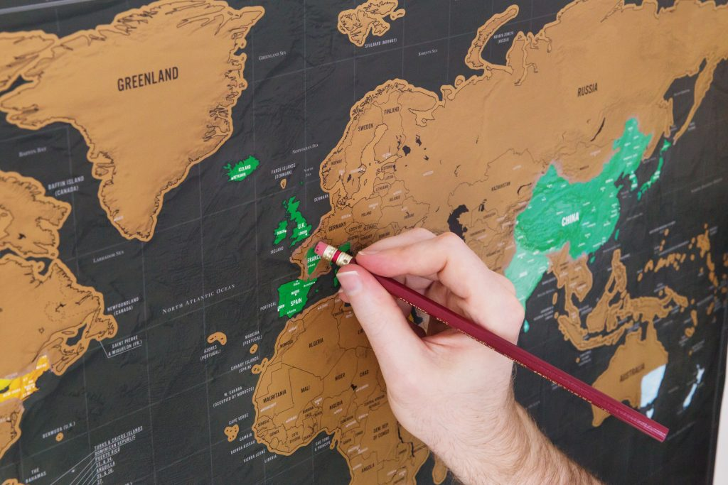 A person is seen scratching France off on their Luckies of London scratch off map