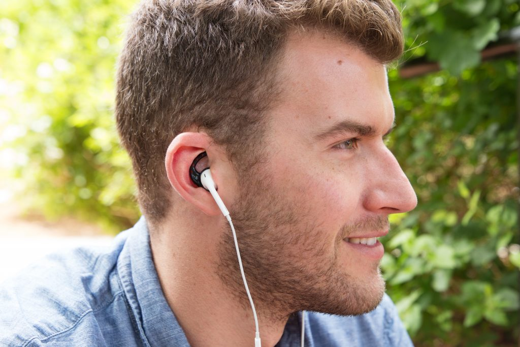 A man is seen listening to music through his Air Pods with the help of Earhoox's soft ,silicone earbud attachments