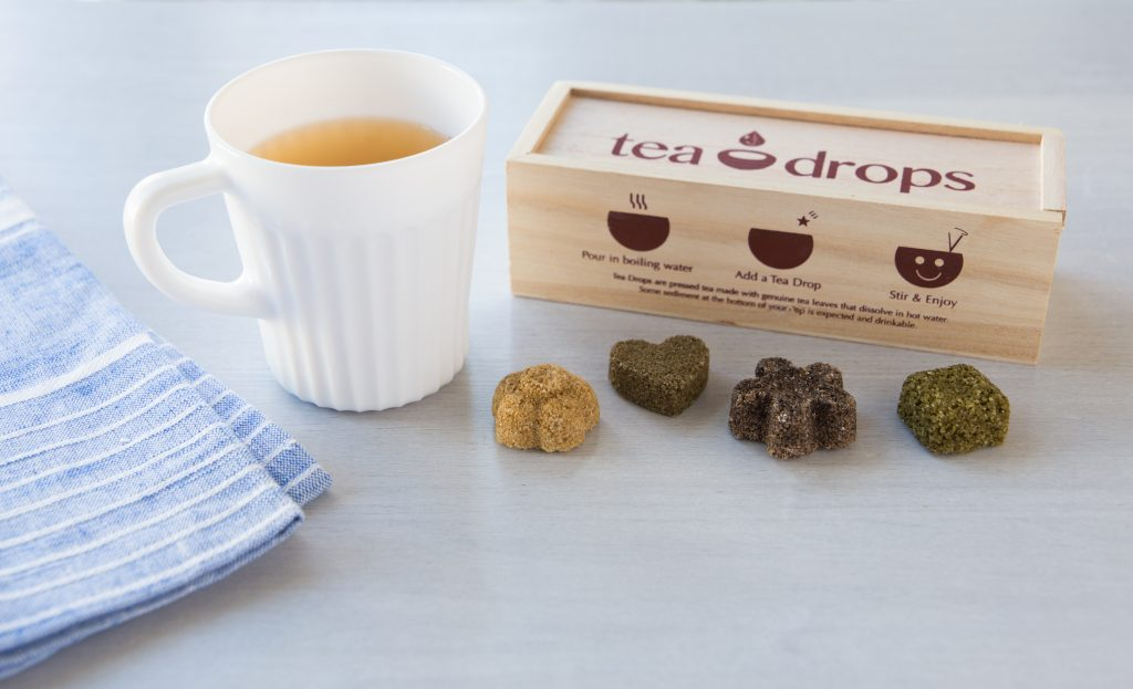 Four pressed Tea Drops sit on a counter next to a steaming cup of tea