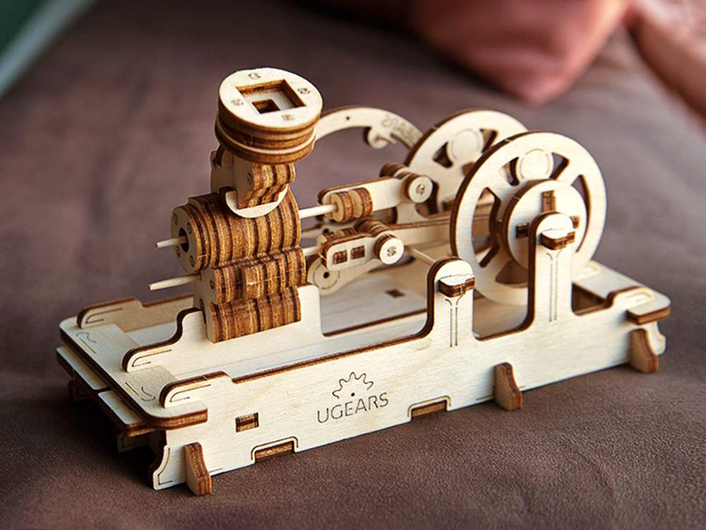 A UGEARS wooden building model of a pneumatic engine sits on a table