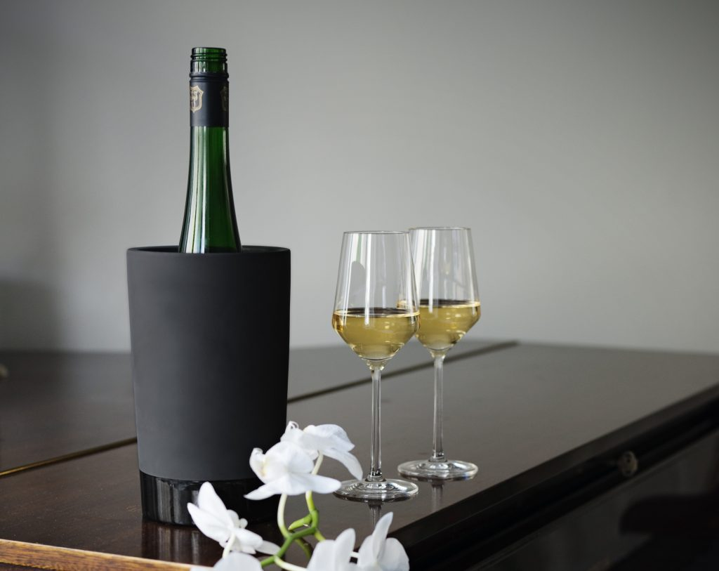 A bottle of wine is seen chilling in a Magisso bottle chiller next to two filled wine glasses