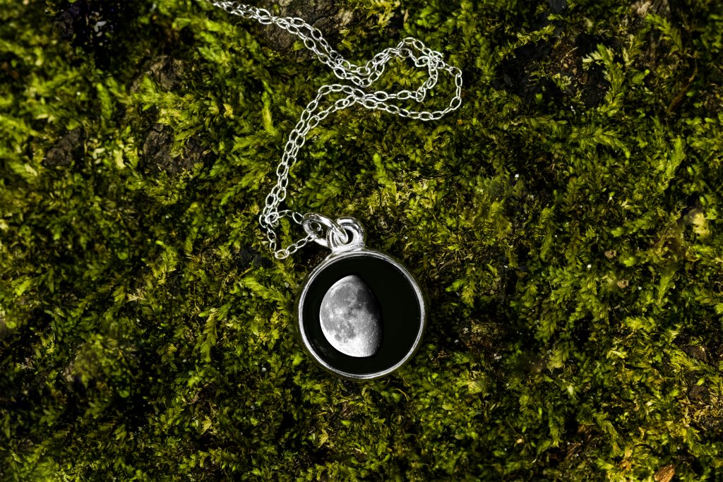 A custom date moon phase necklace from Moonglow lays on a bed of moss