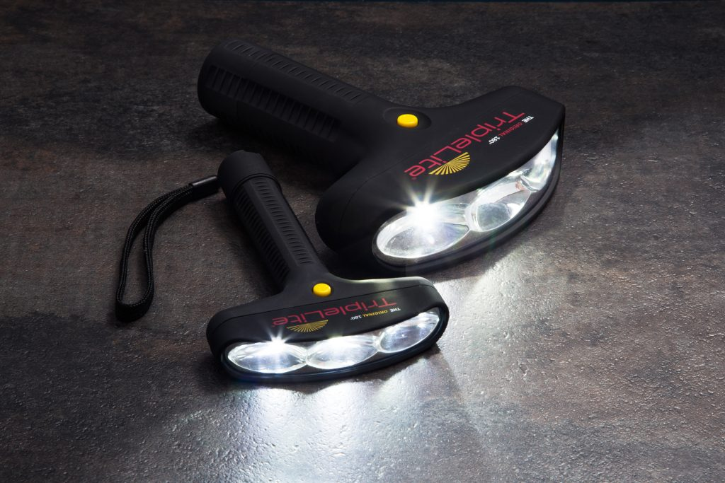 Two TripleLite 180-degree flashlights lay lit on the ground