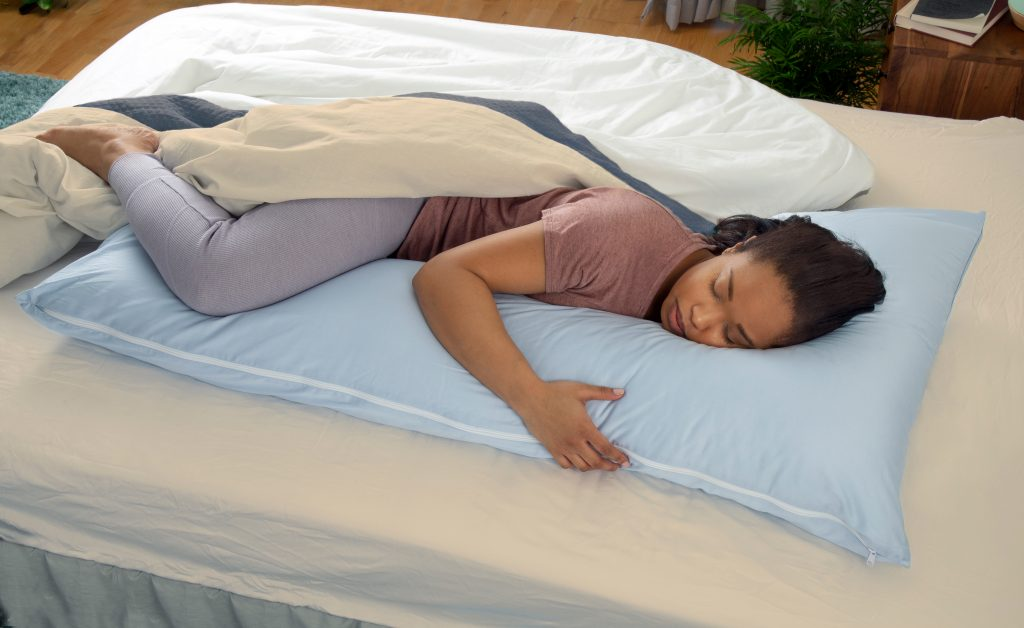 A woman is seen sleeping in bed cuddled up to a blue snuggL l-shaped body pillow