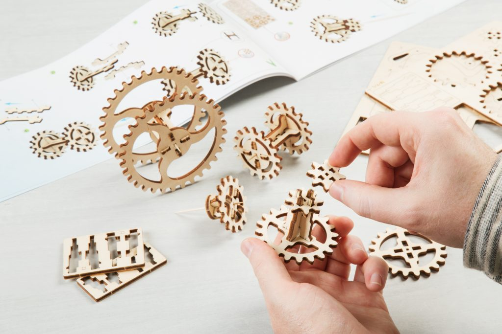 A child is seen piecing together a wooden model building kit from UGEARS