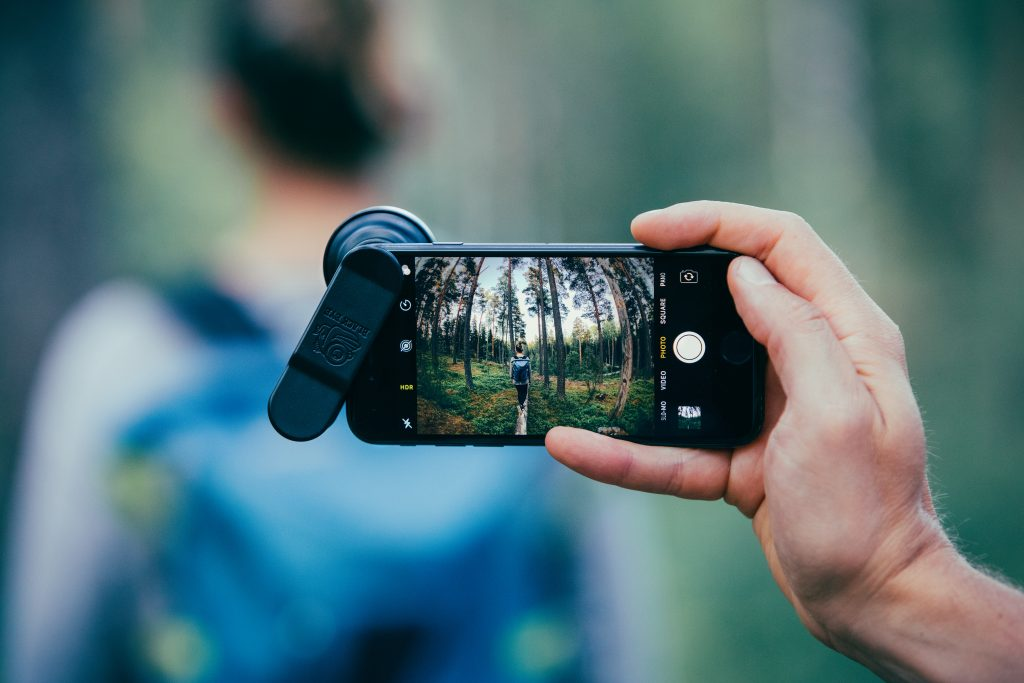 A person is seen taking a photo of a girl in the woods using a Black Eye clip-on smartphone lens