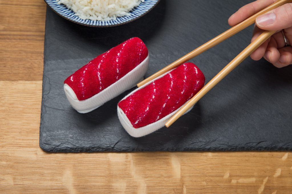 A person is seen using chopsticks to pick up a pair of socks disguised as sushi from Sukeno Socks