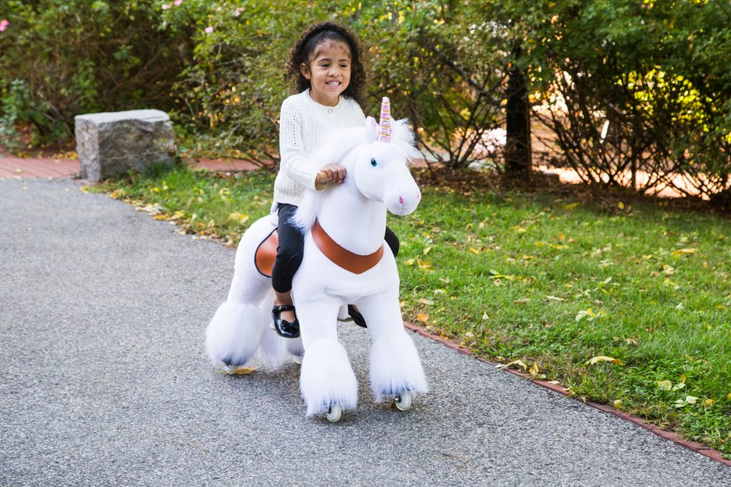 A little girl is seen riding a white unicorn ride-on toy from PonyCycle down the street