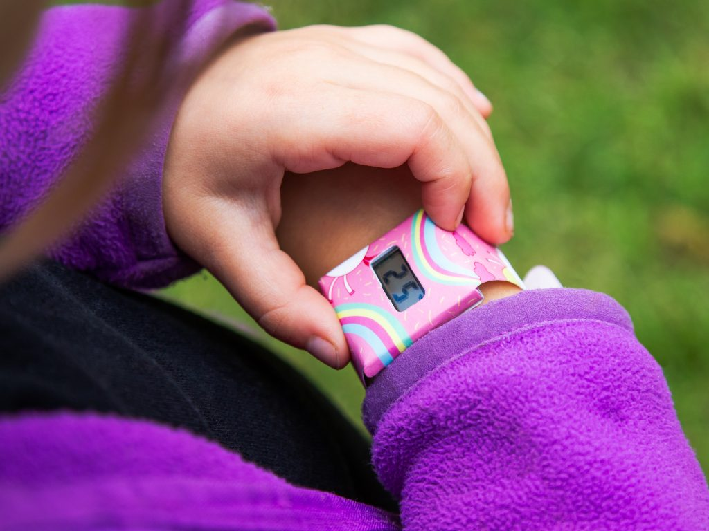 A little girl checks the time on her unicorn printed Tyvek paper watch from I Like Paper