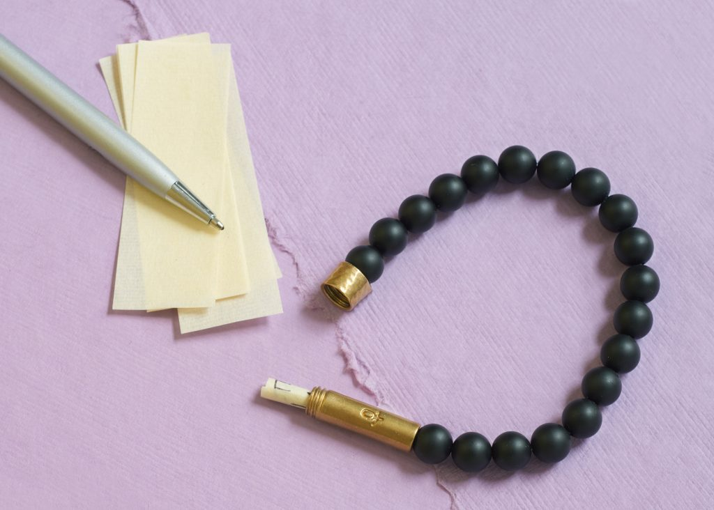 A black Wishbeads bracelet is seen next to pieces of writing paper & a pen
