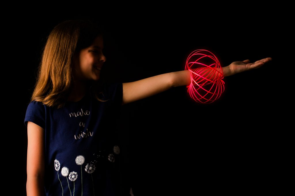 A young girl is seen playing with a glow-in-the-dark MOZI arm spinning toy