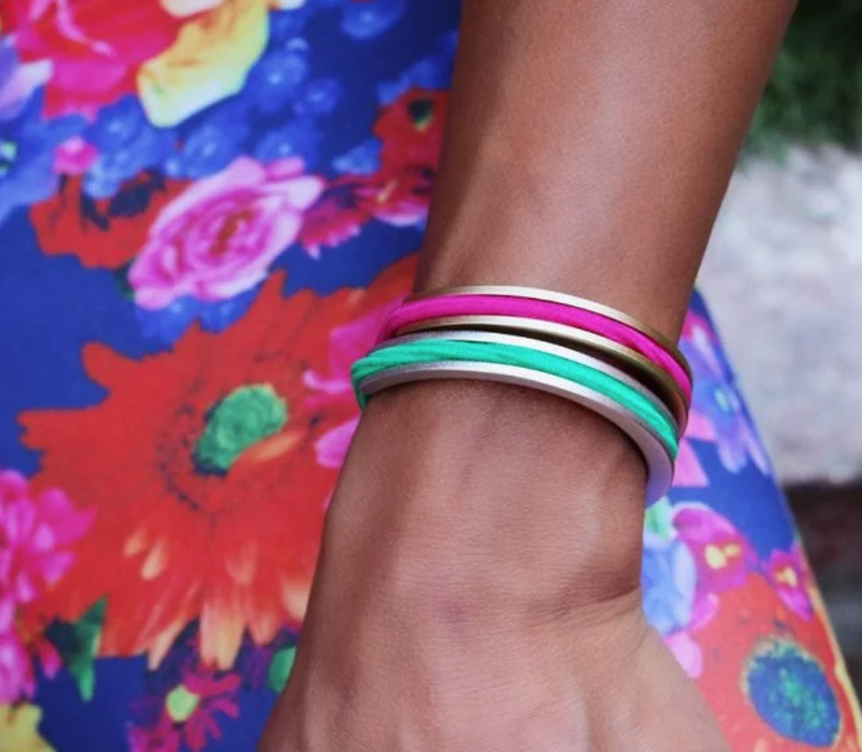 A young girl is seen wearing brightly colored hair elastics secured on her wrist with bittersweet aluminum hair tie bracelets