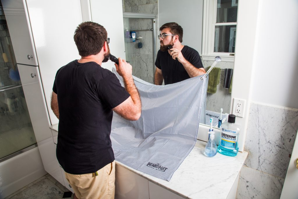 A man is seen trimming his beard in the bathroom using a BeardMat