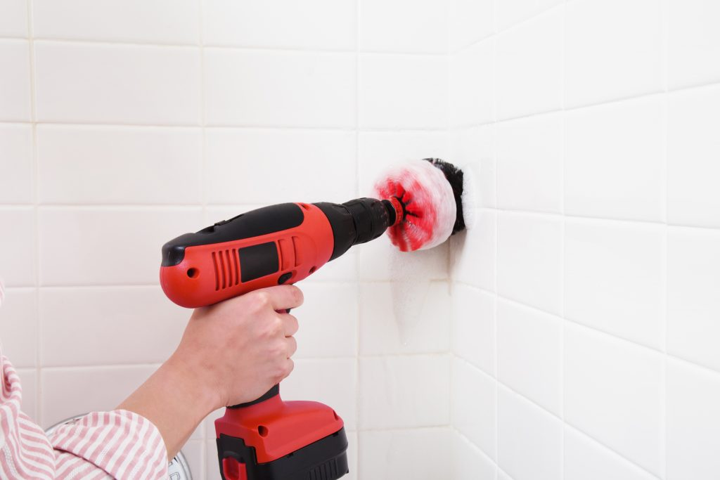 A person is seen scrubbing the grout in their shower with a Drill Brushes scrubbing brush attachment for power drills