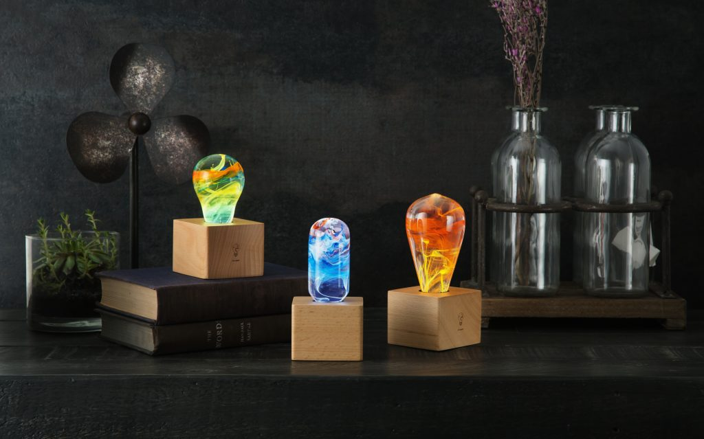 3 different artistic bulb lamps from E.P. Lights sit illuminated on a desk