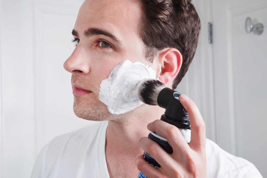 A man is seen lathering his face with shaving cream using Legacy Shave's shaving can brush