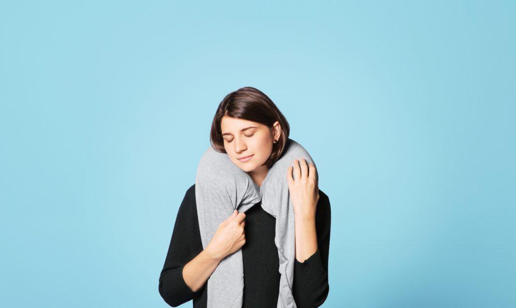 On voit une femme se réchauffer avec son écharpe grise avec un oreiller de voyage intégré