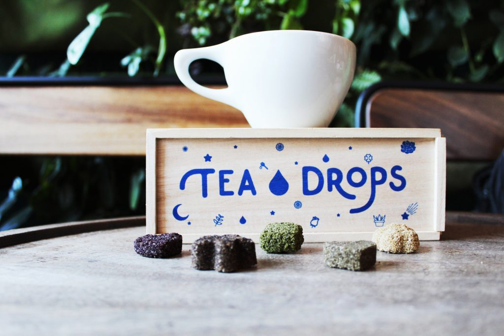5 pressed Tea Drops sit next to a gift box of teas