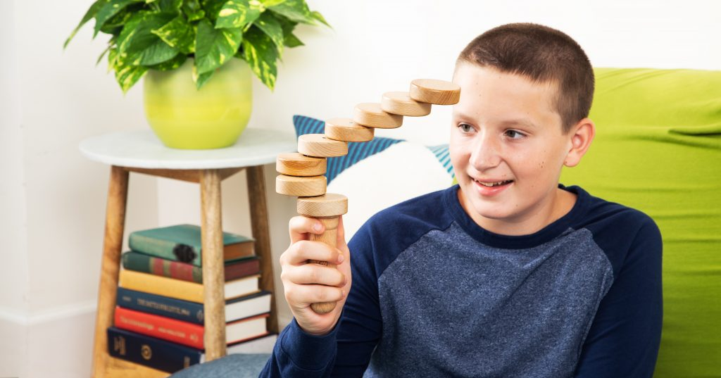 A young boy is seen playing the TrueBalance original magnetic fidget toy
