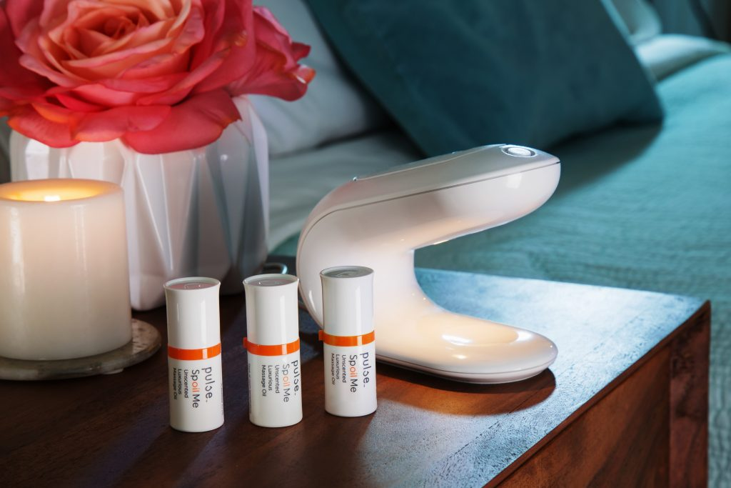 A personal massage oil warming dispenser form Pulse sits on a nightstand with 3 tubes of massage oil